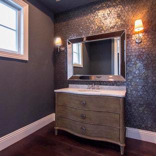Diseño de aseo clásico renovado, pequeño, con armarios tipo mueble, puertas de armario de madera oscura, paredes grises, suelo de madera oscura, lavabo bajoencimera, encimera de mármol y suelo marrón