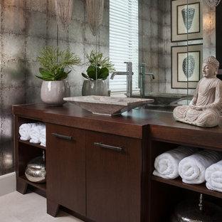 Modelo de aseo asiático con armarios con paneles lisos, puertas de armario de madera en tonos medios, paredes grises, lavabo sobreencimera, encimera de madera, suelo beige y encimeras marrones