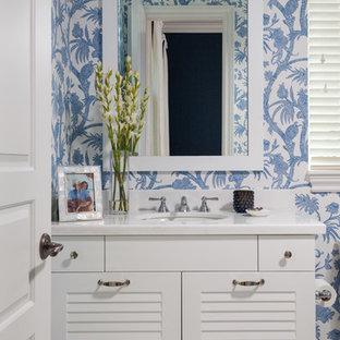 マイアミのビーチスタイルのおしゃれなトイレ・洗面所 (ルーバー扉のキャビネット、白いキャビネット、青い壁、アンダーカウンター洗面器、白い洗面カウンター) の写真