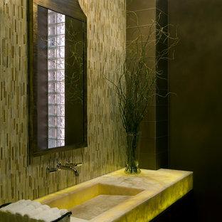 Inspiration pour un petit WC et toilettes minimaliste avec un lavabo intégré, un plan de toilette en onyx, des carreaux en allumettes, un mur jaune, un carrelage beige et un plan de toilette jaune.