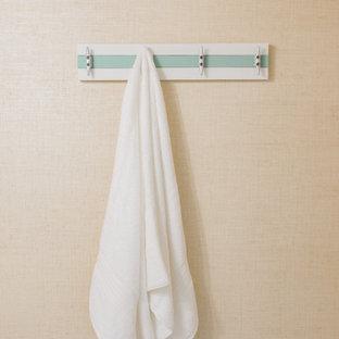 Cette photo montre un WC et toilettes bord de mer de taille moyenne avec des portes de placard blanches, un WC à poser, un sol en carrelage de porcelaine, un plan de toilette blanc, meuble-lavabo sur pied, un plafond en lambris de bois et du papier peint.