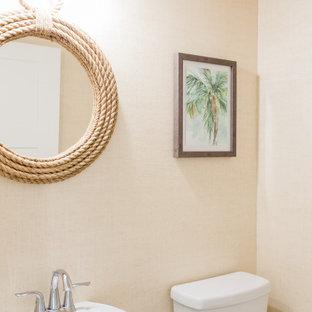 他の地域の中くらいのビーチスタイルのおしゃれなトイレ・洗面所 (白いキャビネット、一体型トイレ、磁器タイルの床、ペデスタルシンク、白い床、白い洗面カウンター、独立型洗面台、塗装板張りの天井、壁紙) の写真