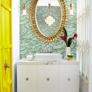 Modelo de aseo retro con armarios con paneles lisos, puertas de armario blancas, suelo de baldosas de porcelana, lavabo sobreencimera, encimera de mármol, paredes multicolor y suelo beige