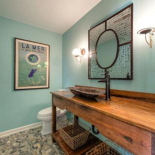 Cette photo montre un WC et toilettes bord de mer de taille moyenne avec un placard sans porte, des portes de placard en bois brun, un WC séparé, un sol en galet, une vasque, un plan de toilette en bois, un mur vert, un sol multicolore et un plan de toilette marron.