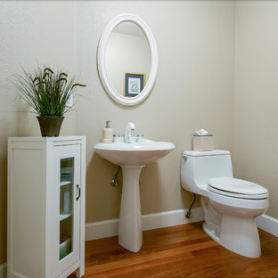 Medium sized classic cloakroom in San Francisco with glass-front cabinets, a one-piece toilet, beige walls, dark hardwood flooring, a pedestal sink and brown floors.