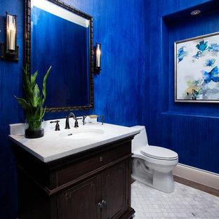Immagine di un bagno di servizio mediterraneo con consolle stile comò, ante in legno bruno, WC monopezzo, pareti blu, lavabo sottopiano e pavimento grigio