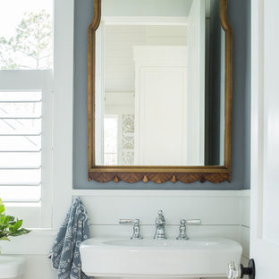 Design ideas for a small beach style powder room in Charleston with grey walls, a pedestal sink and light hardwood floors.