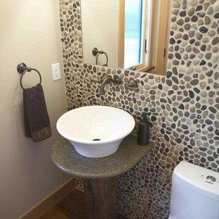 На фото: маленький туалет в стиле рустика с настольной раковиной, галечной плиткой, столешницей из гранита, раздельным унитазом, бежевыми стенами, серой плиткой, полом из бамбука, коричневым полом и зеленой столешницей