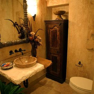 Ispirazione per un bagno di servizio stile rurale di medie dimensioni con WC a due pezzi, pareti beige, pavimento in travertino, lavabo a bacinella e top in pietra calcarea