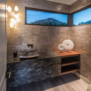 Inspiration for a large contemporary beige tile and mosaic tile medium tone wood floor and beige floor powder room remodel in Phoenix with open cabinets, a one-piece toilet, beige walls, a vessel sink, granite countertops and black countertops