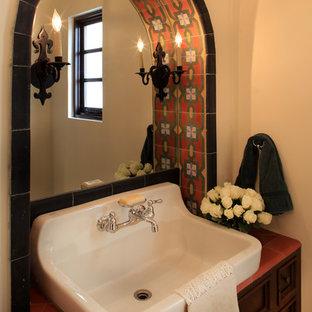 Imagen de aseo mediterráneo con encimera de azulejos y lavabo de seno grande