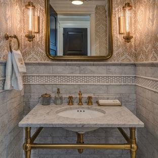 他の地域の中くらいのトラディショナルスタイルのおしゃれなトイレ・洗面所 (オープンシェルフ、黄色いキャビネット、一体型トイレ、グレーのタイル、大理石タイル、黄色い壁、大理石の床、ペデスタルシンク、大理石の洗面台、グレーの床、グレーの洗面カウンター) の写真