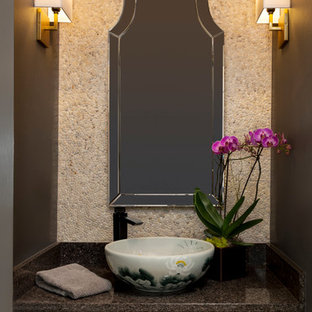 Photo of a world-inspired cloakroom in Denver with freestanding cabinets, beige cabinets, a two-piece toilet, beige tiles, stone tiles, grey walls, medium hardwood flooring, a vessel sink, granite worktops, brown floors and red worktops.