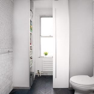 ニューヨークの小さいモダンスタイルのおしゃれなトイレ・洗面所 (一体型トイレ、グレーのタイル、モザイクタイル、白い壁、磁器タイルの床、壁付け型シンク、黒い床、白い洗面カウンター、独立型洗面台、羽目板の壁) の写真