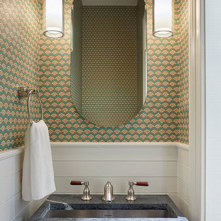 This is an example of a small transitional powder room in New York with multi-coloured walls, an undermount sink and soapstone benchtops.