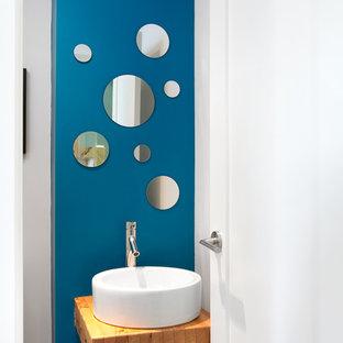 На фото: туалеты в современном стиле с настольной раковиной, столешницей из дерева, синими стенами и коричневой столешницей