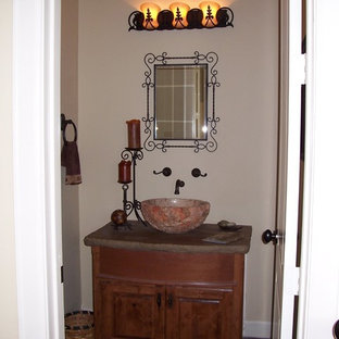 This is an example of a small classic cloakroom in Houston with a vessel sink, raised-panel cabinets, medium wood cabinets, a two-piece toilet, beige walls and slate flooring.