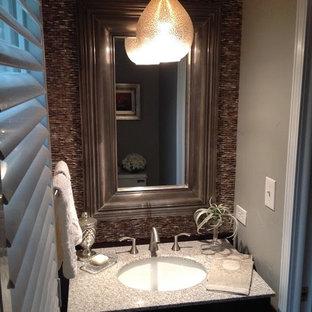 Réalisation d'un petit WC et toilettes tradition avec un carrelage marron, un carrelage de pierre, un mur gris, un lavabo encastré et un plan de toilette en terrazzo.