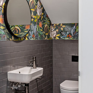 Idee per un piccolo bagno di servizio design con piastrelle grigie, piastrelle in ceramica, pareti verdi, pavimento alla veneziana, lavabo sospeso e pavimento grigio