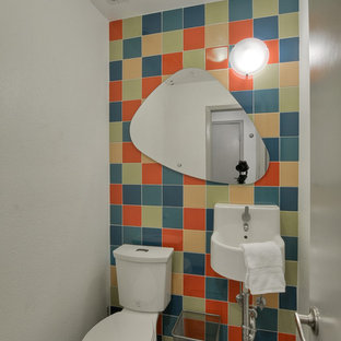 Small contemporary cloakroom in Dallas with ceramic tiles, a wall-mounted sink, multi-coloured tiles, a two-piece toilet, porcelain flooring and multi-coloured walls.