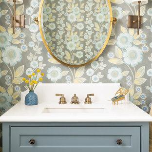 Idee per un bagno di servizio stile marinaro con ante a filo, ante blu, pareti multicolore, lavabo sottopiano e top bianco