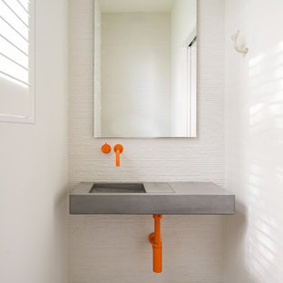 Diseño de aseo costero, pequeño, con paredes blancas, lavabo suspendido, encimera de cemento y suelo gris
