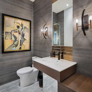Réalisation d'un WC et toilettes design de taille moyenne avec un placard à porte plane, un WC à poser, un mur gris, un sol en carrelage de céramique, un sol gris, des portes de placard en bois sombre, carrelage en métal et un lavabo intégré.