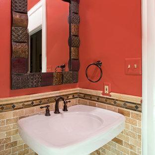 Неиссякаемый источник вдохновения для домашнего уюта: туалет в стиле фьюжн с раковиной с пьедесталом, унитазом-моноблоком, бежевой плиткой, красными стенами и каменной плиткой