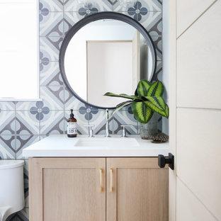 Maritime Gästetoilette mit Schrankfronten im Shaker-Stil, hellen Holzschränken, Toilette mit Aufsatzspülkasten, blauen Fliesen, grauen Fliesen, weißen Fliesen, blauer Wandfarbe, Fliesen in Holzoptik, Unterbauwaschbecken, braunem Boden, weißer Waschtischplatte und eingebautem Waschtisch in Orange County