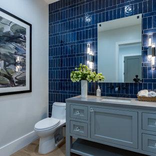 ロサンゼルスの中くらいのトランジショナルスタイルのおしゃれなトイレ・洗面所 (シェーカースタイル扉のキャビネット、青いキャビネット、一体型トイレ、青いタイル、セラミックタイル、グレーの壁、淡色無垢フローリング、アンダーカウンター洗面器、ベージュの床、グレーの洗面カウンター、造り付け洗面台、折り上げ天井) の写真