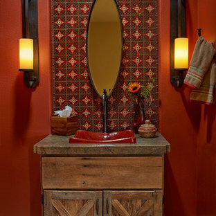 Photo of a small rustic cloakroom in Los Angeles with a vessel sink, freestanding cabinets, medium wood cabinets, quartz worktops, multi-coloured tiles, ceramic tiles, red walls and ceramic flooring.