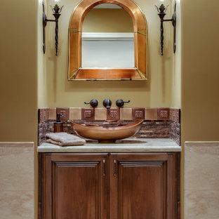 На фото: со средним бюджетом маленькие туалеты в стиле фьюжн с фасадами с выступающей филенкой, фасадами цвета дерева среднего тона, унитазом-моноблоком, коричневой плиткой, полом из травертина, настольной раковиной, мраморной столешницей, бежевыми стенами и удлиненной плиткой