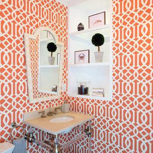 Cette image montre un très grand WC et toilettes traditionnel avec un WC à poser, un mur orange, un sol en bois foncé, un plan vasque et un sol marron.