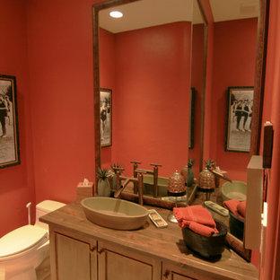 Modelo de aseo ecléctico con lavabo sobreencimera, armarios con paneles empotrados, puertas de armario de madera oscura, encimera de madera, sanitario de una pieza y paredes rojas