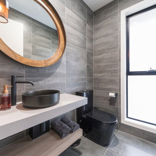 Photo of a mid-sized contemporary powder room in Gold Coast - Tweed with grey cabinets, a one-piece toilet, gray tile, a console sink and a floating vanity.