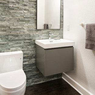 Свежая идея для дизайна: маленький туалет в стиле современная классика с плоскими фасадами, серыми фасадами, унитазом-моноблоком, серой плиткой, каменной плиткой, белыми стенами, темным паркетным полом и подвесной раковиной - отличное фото интерьера