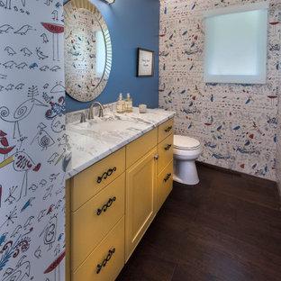На фото: туалет среднего размера в стиле фьюжн с плоскими фасадами, желтыми фасадами, раздельным унитазом, разноцветными стенами, темным паркетным полом, врезной раковиной, мраморной столешницей, коричневым полом и белой столешницей с