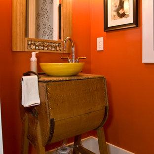 Kleine Eklektische Gästetoilette mit verzierten Schränken, hellbraunen Holzschränken, oranger Wandfarbe, Mosaik-Bodenfliesen, Aufsatzwaschbecken, Waschtisch aus Holz und buntem Boden in Charlotte