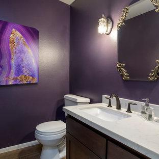 ロサンゼルスの中くらいのトランジショナルスタイルのおしゃれなトイレ・洗面所 (フラットパネル扉のキャビネット、濃色木目調キャビネット、分離型トイレ、紫の壁、磁器タイルの床、アンダーカウンター洗面器、クオーツストーンの洗面台、ベージュの床) の写真