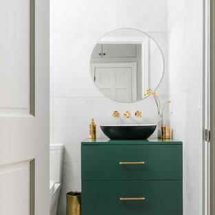 Modelo de aseo actual con armarios con paneles lisos, puertas de armario verdes, baldosas y/o azulejos grises, lavabo sobreencimera, suelo gris y encimeras verdes