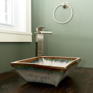 Imagen de aseo contemporáneo con paredes verdes, lavabo sobreencimera y encimera de madera