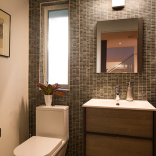 Design ideas for a small modern cloakroom in New York with flat-panel cabinets, medium wood cabinets, a one-piece toilet, multi-coloured tiles, porcelain tiles, white walls, pebble tile flooring, an integrated sink, solid surface worktops, beige floors and white worktops.