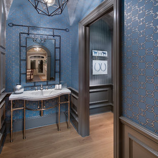Powder room - beach style light wood floor powder room idea in Cleveland with multicolored walls and a console sink