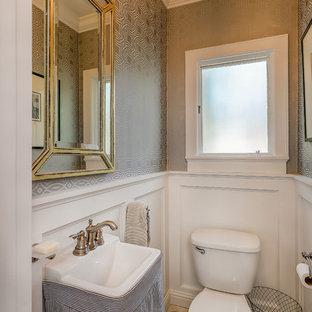 Klassisk inredning av ett litet vit vitt toalett, med en toalettstol med separat cisternkåpa, grå väggar, marmorgolv, ett piedestal handfat, bänkskiva i akrylsten och vitt golv