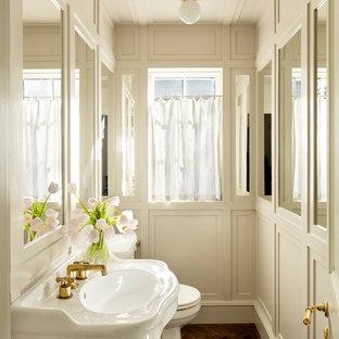 Exempel på ett mellanstort klassiskt toalett, med vita väggar, mörkt trägolv, ett konsol handfat och brunt golv