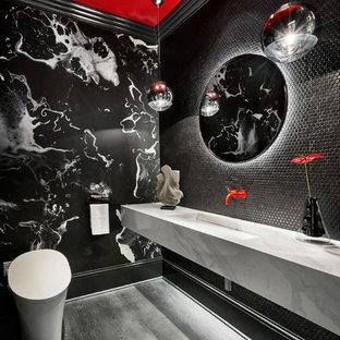 Idées déco pour un WC et toilettes contemporain avec un WC suspendu, un carrelage noir, carrelage en mosaïque, un mur noir, un lavabo intégré, un sol gris et un plan de toilette blanc.