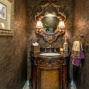 Cette image montre un petit WC et toilettes méditerranéen avec un placard en trompe-l'oeil, des portes de placard en bois sombre, un mur marron, un lavabo encastré et un sol en travertin.