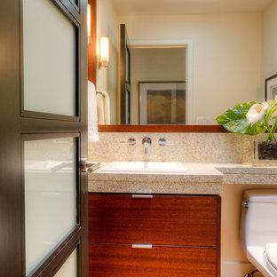 Идея дизайна: маленький туалет в стиле ретро с плоскими фасадами, темными деревянными фасадами, унитазом-моноблоком, бежевой плиткой, каменной плиткой, бежевыми стенами, паркетным полом среднего тона, накладной раковиной, столешницей из гранита, коричневым полом и серой столешницей