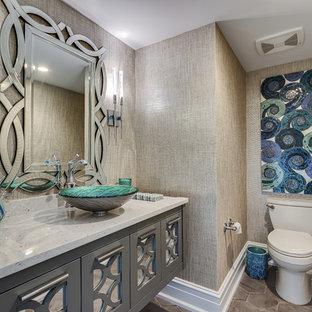 Idee per un piccolo bagno di servizio stile marinaro con consolle stile comò, ante grigie, WC monopezzo, piastrelle grigie, piastrelle in ceramica, pareti beige, pavimento con piastrelle in ceramica, lavabo a bacinella, top in superficie solida e pavimento grigio