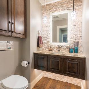 Неиссякаемый источник вдохновения для домашнего уюта: маленький туалет в стиле современная классика с фасадами с выступающей филенкой, темными деревянными фасадами, инсталляцией, бежевой плиткой, каменной плиткой, серыми стенами, паркетным полом среднего тона, врезной раковиной и столешницей из гранита